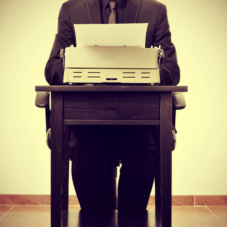 bureaucrat: man typing on an old typewriter, with a retro effect Stock Photo