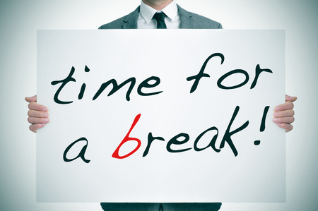 businessman holding a signboard with the text time for a break written in it photo