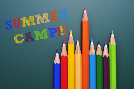 campamento: campamento de verano, el texto escrito en una pizarra y unos lápices de colores de diferentes colores Foto de archivo