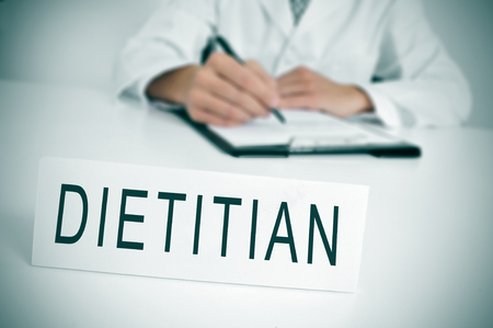 a doctor sitting in a desk with a nameplate in front of him with the word dietitian written in it photo