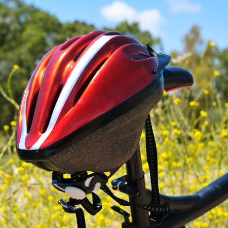 casco rojo: primer plano de un casco rojo que cuelga en una bicicleta de montaña en un paisaje de primavera Foto de archivo