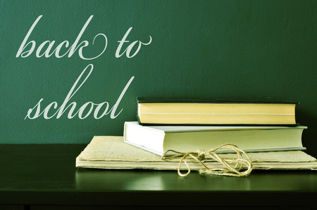 back to school supplies: some books on a desk and the text back to school written on a green chalkboard