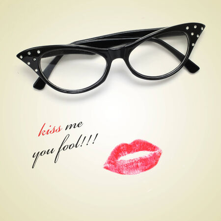 lipstick kiss mark: sentence kiss me you fool and retro-styled eyeglasses and a lipstick mark Stock Photo