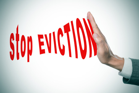 eviction: man hand stopping the text stop eviction