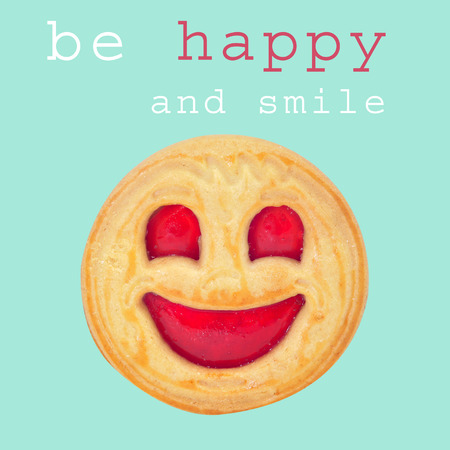 a biscuit with a smiley biscuit and the sentence be happy and smile on a blue background photo