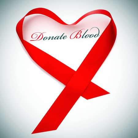 the sentence donate blood and a red ribbon forming a heart photo