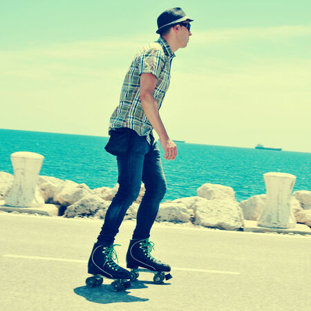 rollerskating: a young man roller skating near the sea, with a cross-processed effect Stock Photo