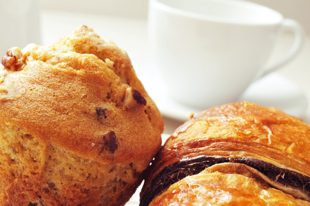 closeup of a chocolate croissant and a muffin on a set table with a cup of coffee in the background photo