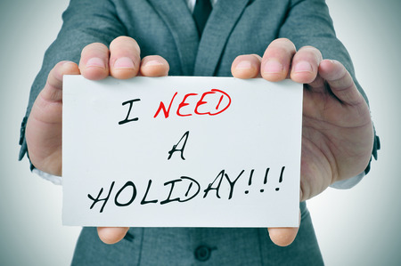need: businessman showing a signboard with the text I need a holiday written in it