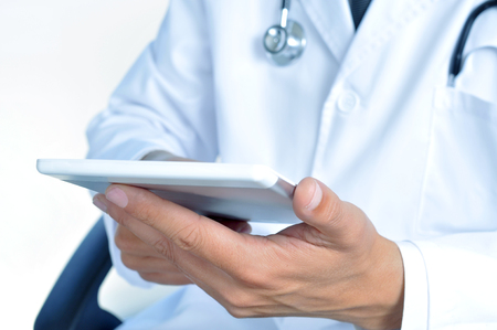 closeup of a doctor checking out his tablet photo