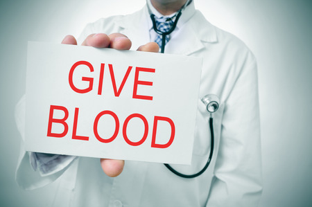 a doctor showing a signboard with the sentence give blood written in it photo