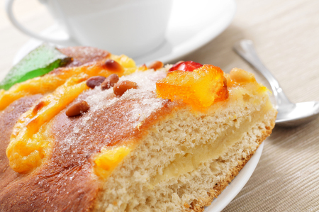 sant: a piece of coca de Sant Joan, a typical sweet flat cake from Catalonia, Spain, eaten on Saint Johns Eve, and a cup of hot chocolate in the background