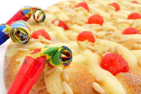 sant: closeup of a coca de Sant Joan, a typical sweet flat cake from Catalonia, Spain, eaten on Saint Johns Eve, and some party horns Stock Photo