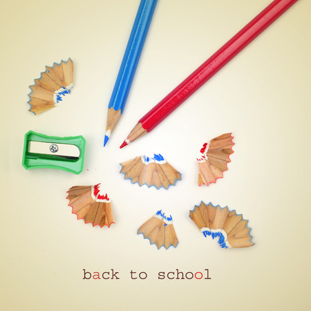 a sharpener, pencil crayons of different colors and the sentence back to school on a beige background, with a retro effect photo