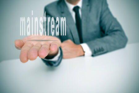 mainline: man wearing a suit sitting in a desk holding the word mainstream in his hands