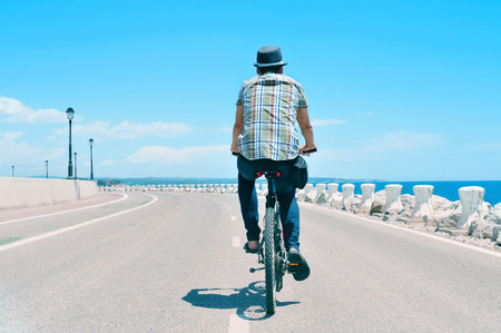 young man riding a bike on a no traffic road near the sea Stock Photo