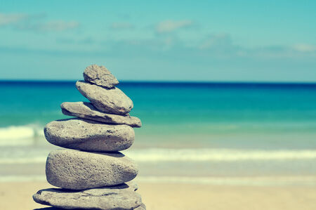 stack of balanced stones in a white sand beach, with a cross-processed effect photo