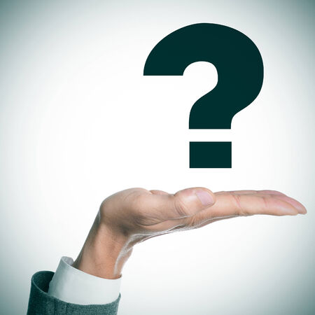 existentialism: the hand of a man wearing a suit holding a question mark Stock Photo