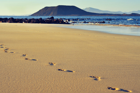 footprints on a white sand beach in Corralejo in Fuerteventura, Canary Islands, Spain, with Lobos Island and Lanzarote Island in the background Stock Photo - 29991244