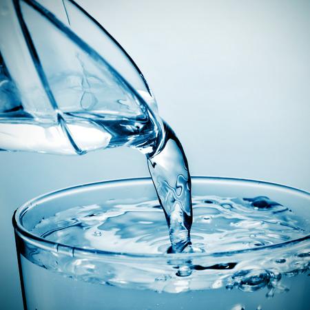 Nahaufnahme von einem erfrischenden Glas Wasser, das aus einem Krug gefüllt ist Standard-Bild - 29805161