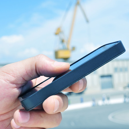 closeup of the hand of a man using a smartphone in an industrial park photo