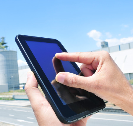 closeup of the hands of a man using a tablet in an industrial park photo