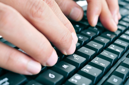closeup of the hands of a man typing on a computer keyboard photo
