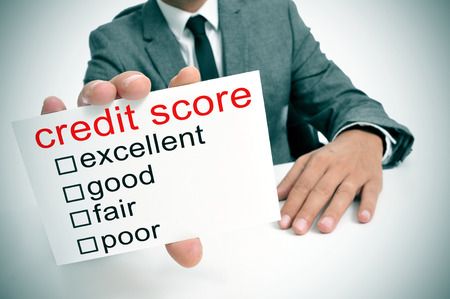 bank rate: man in suit showing a signboard with the different ranges of the credit score: excellent, good, fair and poor Stock Photo