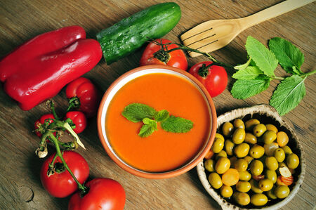 andalusian cuisine: a bowl with spanish gazpacho, some vegetables to prepare it such as tomato, red pepper and cucumber, and a plate with gazpachas olives on a rustic wooden table