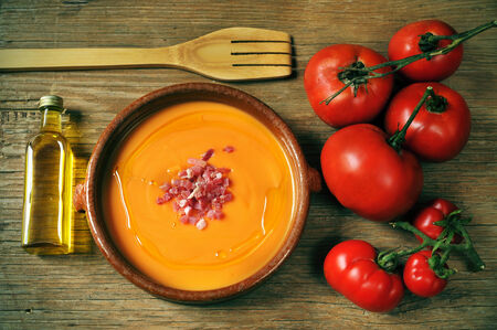 an earthenware bowl with spanish salmorejo, tomatoes and a bottle of olive oil on a rustic wooden table Reklamní fotografie
