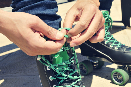 rollerskater: closeup of the hands of a young man tying his roller skates, with a filter effect