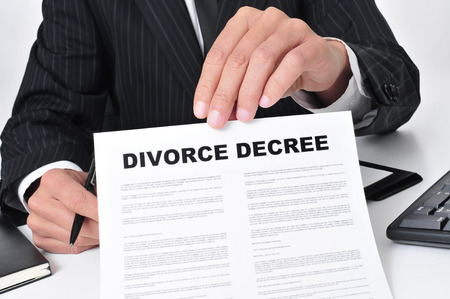 divorce court: closeup of a lawyer sitting in his desk showing a divorce decree