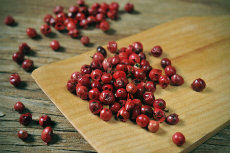 peppertree: a pile of pink peppercorns on a rustic wooden table