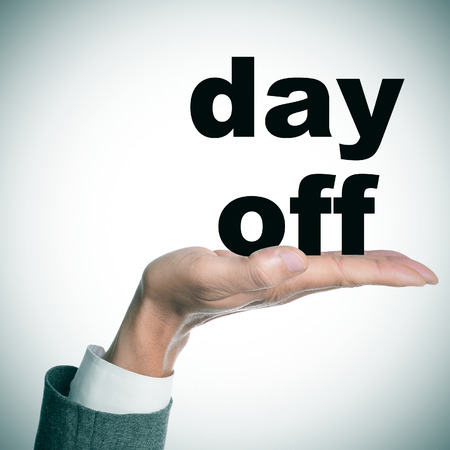 day off: the hand of a man wearing a suit holding the text day off