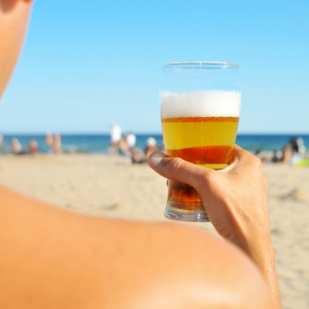 a young man having a refreshing beer on the beach Stock Photo