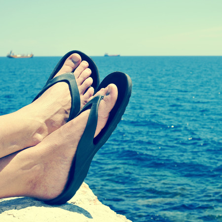 beach feet: closeup of the feet of a man with flip-flops who is relaxing near the ocean in the summer, with a retro filter effect