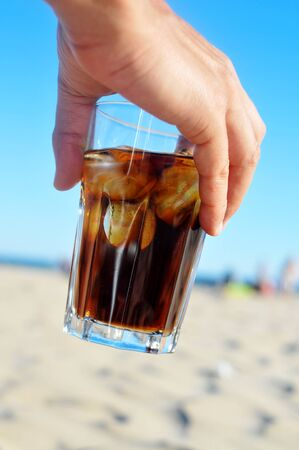 thirsting: closeup of the hand of a young man with a glass with refreshing cola drink on the beach