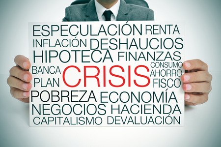 capitalism: a businessman holding a signboard with different terms in spanish related to the economic crisis concept Stock Photo