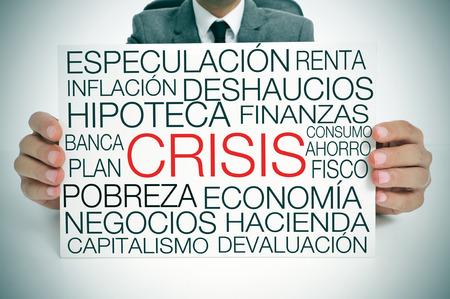 crisis economica: un hombre de negocios que sostiene un letrero con diferentes términos en español relacionados con el concepto de la crisis económica Foto de archivo