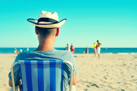 chilling out: a young man with a straw hat relaxing on the beach Stock Photo
