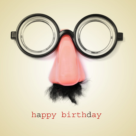 sentence happy birthday and fake eyeglasses, nose and mustache on a beige background, with a retro effect photo