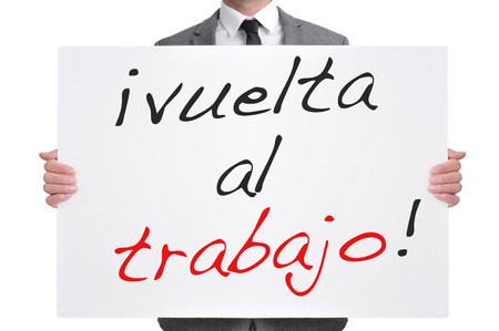 businessman holding a signboard with the text vuelta al trabajo, back to work in spanish, written in it