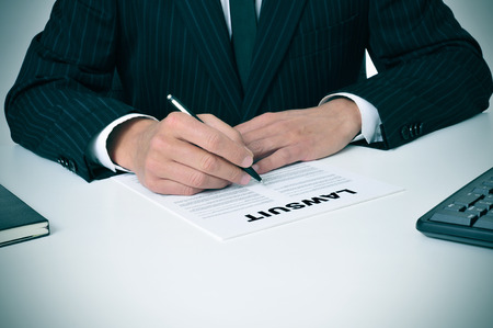 a lawyer in his office with a document with the text lawsuit written in it photo