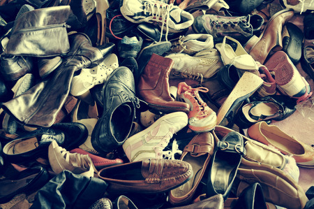used clothes: a pile of second hand shoes in a flea market, with a retro filter effect