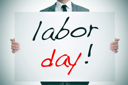 work force: a man wearing a suit holding a signboard with the text labor day written in it