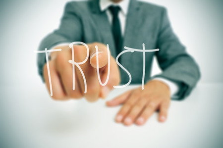 on the foreground: businessman sitting in a desk pointing the word trust written in the foreground