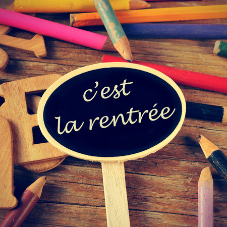 the sentence cest la rentree, back to school written in french in a blackboard label, on a wooden table and colored pencils of different colors photo