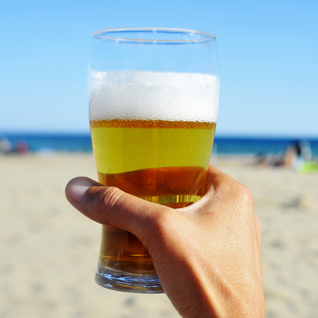 young man hand holding a refreshing beer on the beach photo