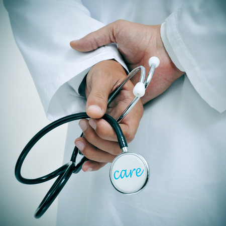 health care: a doctor holding a stethoscope with the word care written in it