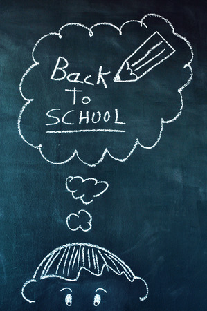 drawing of a boy with chalk in a chalkboard and a thought bubble with the text back to school written in it photo